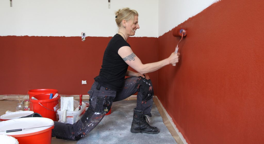 Silke streicht die Wand rot